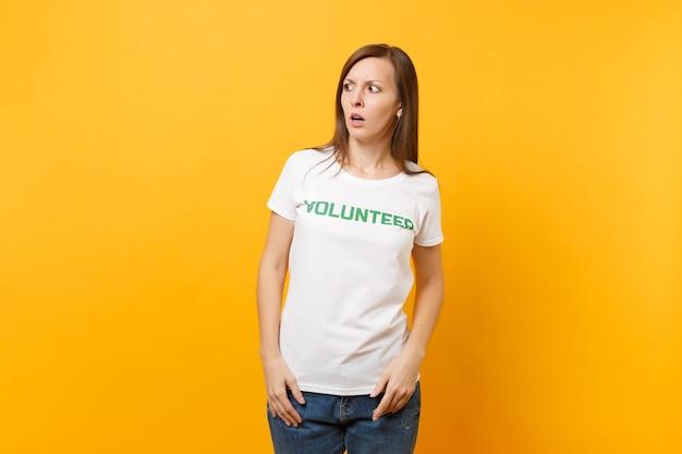 Portret van bang geschokt bang jonge vrouw in wit t-shirt met schriftelijke inscriptie groene titel vrijwilliger geïsoleerd op gele achtergrond. vrijwillige gratis hulp, liefdadigheidswerkconcept.