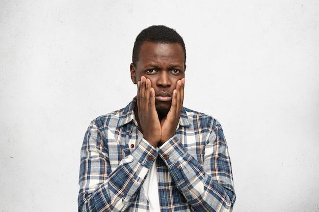 Portret van bang jonge afro-amerikaanse man met kiespijn met gefrustreerde bange blik