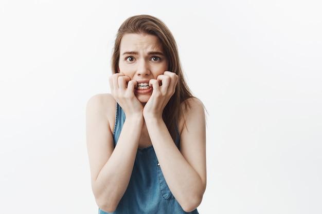 Portret van bang knappe jonge vrouw met donker lang haar in blauwe kleren knagende handen, met angstige uitdrukking, nerveus en onzeker over het volgende examen.