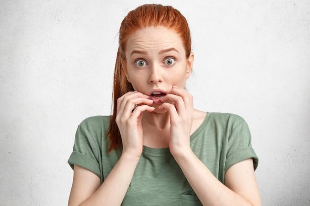 Portret van bang mooie roodharige jonge vrouw kijkt met verbazing en ogen schoot uit, heeft geschokt uitdrukking, vormt tegen wit beton