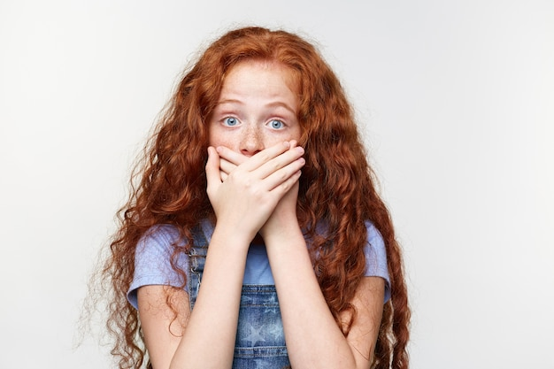Portret van bang schattig sproeten klein meisje met rood haar, hoort een vreselijk verhaal, bedekte mond met handpalmen, staat over een witte muur met wijd open ogen met een geschrokken uitdrukking.