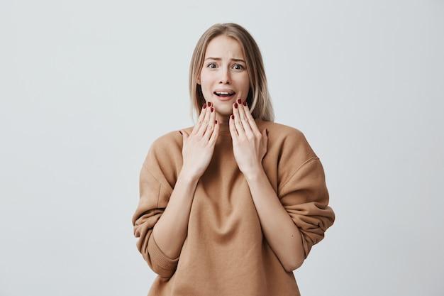 Portret van bang verbaasd jonge vrouw met geverfd blond haar, kijkt met angstige uitdrukking