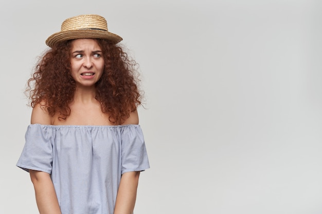 Portret van bang, volwassen roodharig meisje met krullend haar. gestreepte blouse en hoed met blote schouders. heeft medelijden met je. kijken naar rechts op kopie ruimte, geïsoleerd over witte muur