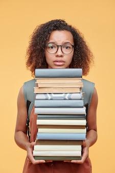 Portret van bang zwart studentenmeisje in oogglazen die met hoop van leerboeken van de werklastholding tegen gele achtergrond wordt verward