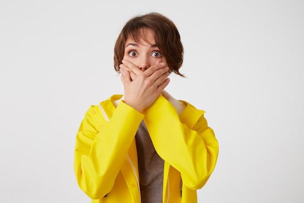 Portret van bange kortharige krullende vrouw in gele regenjas, hoorde een vreselijk verhaal, bedekte mond met handpalmen, staat over een witte muur met wijd open ogen met een geschrokken uitdrukking.