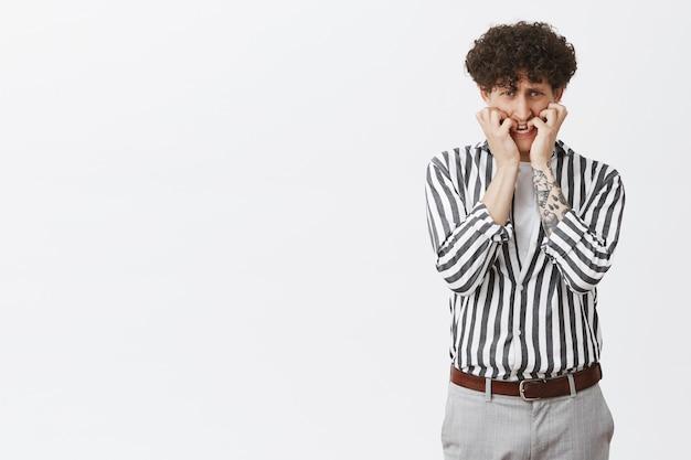 Portret van bange mannelijke lafaard met krullend haar tatoeages en snor vingernagels bijten op zoek onder voorhoofd bang en nerveus in paniek wordt doodsbang staande in gestreepte shirt en broek