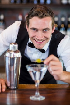 Portret van barman die cocktail met olijf versieren