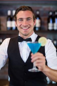 Portret van barman die een blauwe martini dient
