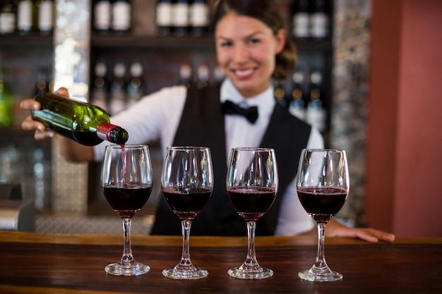 Portret van barman die een rode wijn in het glas gieten