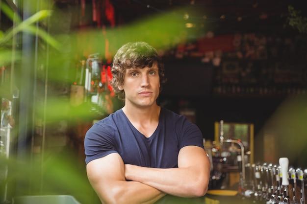 Portret van barman die zich met gekruiste wapens bevindt