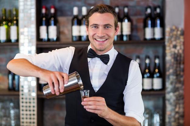Portret van barman gietende tequila in geschoten glas