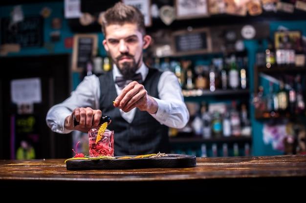 Portret van barman maakt een show die een cocktail in de kroeg maakt