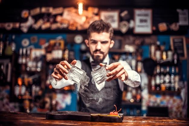 Portret van barman voegt ingrediënten toe aan een cocktail terwijl hij in de buurt van de toog in de pub staat