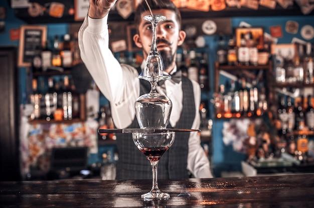 Portret van bartending demonstreert het proces van het maken van een cocktail