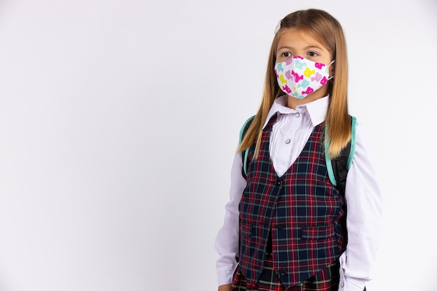 Portret van basisschoolmeisje dat met gezichtsmasker terug naar school gaat na covid-19 quarantaine en lockdown. geïsoleerd op grijze muur met lege zijruimte.