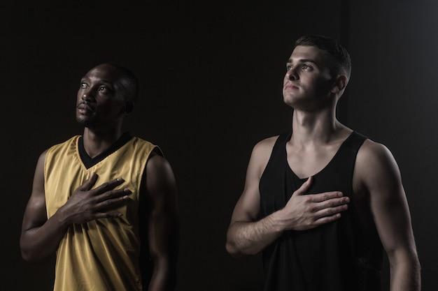 Portret van basketbalspelers die omhooggaand en hand op hart kijken zetten