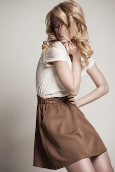 Portret van beautyful poseren blonde vrouw met lang krullend haar op witte achtergrond