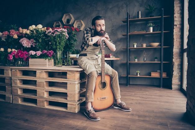 Portret van bebaarde bloemist poseren in zijn bloemenwinkel met gitaar