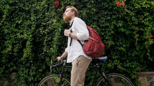 Portret van bebaarde hipster man wandelen met vintage fiets in het park.
