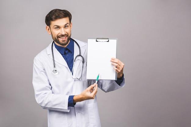 Portret van bebaarde lachende stagiair, die het klembord met leeg papier houdt. dokter draagt witte uniform, staat over geïsoleerde grijze achtergrond, met blanco.