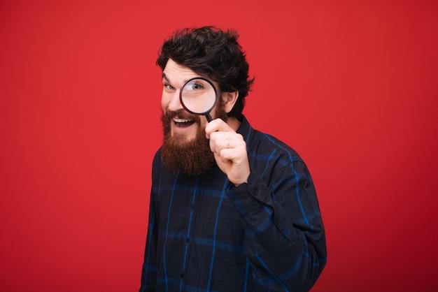 Portret van bebaarde man kijkt door een vergrootglas over rode muur