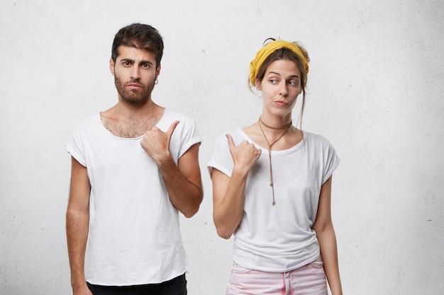 Portret van bebaarde man met trendy kapsel en vrouw met gele sjaal op hoofd wijzend met hun wijsvingers achter hun rug met mysterieuze blik