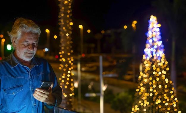 Portret van bebaarde senior man met wit haar met behulp van slimme telefoon buiten in de nacht met verlichte kerstboom achter hem. concept van ouderen tech en sociaal