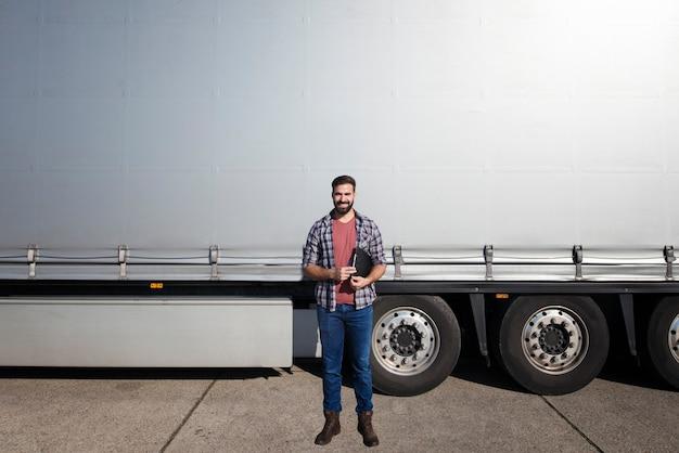 Portret van bebaarde vrachtwagenchauffeur van middelbare leeftijd die zich voor vrachtwagenaanhangwagen bevindt tegen grijs glanzend geteerd zeildoek