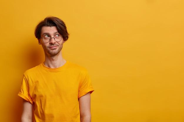 Portret van bedachtzame serieuze man ergens opzij geconcentreerd, denkt hoe beter te handelen, draagt grote ronde bril en casual t-shirt, geïsoleerd op gele muur, lege ruimte. monochroom
