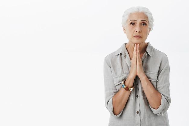 Portret van bedelende oude dame die somber kijkt, hulp nodig heeft