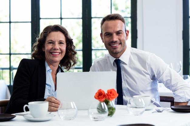 Portret van bedrijfscollega's die laptop met behulp van terwijl het hebben van een vergadering