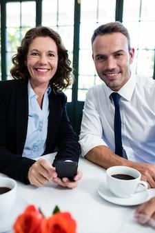 Portret van bedrijfscollega's met mobiele telefoon