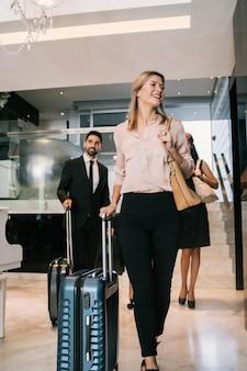 Portret van bedrijfsmensen die bij hotel aankomen en door de lobby met hun bagage lopen. reis- en bedrijfsconcept.
