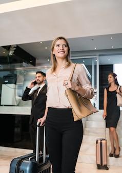 Portret van bedrijfsmensen die bij hotel aankomen en door de lobby met hun bagage lopen.