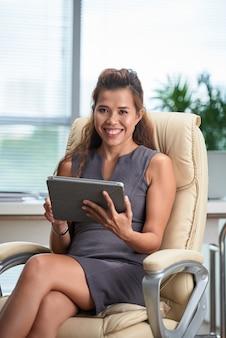 Portret van bedrijfsvrouw die aan tabletcomputer als haar bureauvoorzitter werkt