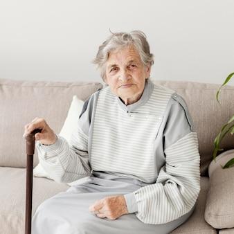 Portret van bejaarde oma zittend op de bank
