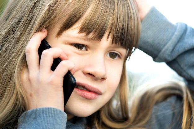Portret van beklemtoond kindmeisje met lang haar dat op celtelefoon spreekt. kleine vrouwelijke jongen communiceren via smartphone. kinderen communicatieconcept.