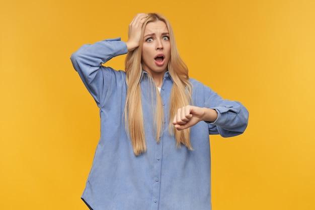 Portret van beklemtoond meisje met blond lang haar. het dragen van een blauw shirt. mensen en emotie concept. haar hoofd aanraken, polshorloge controleren, tijd. kijken naar de camera, geïsoleerd op oranje achtergrond