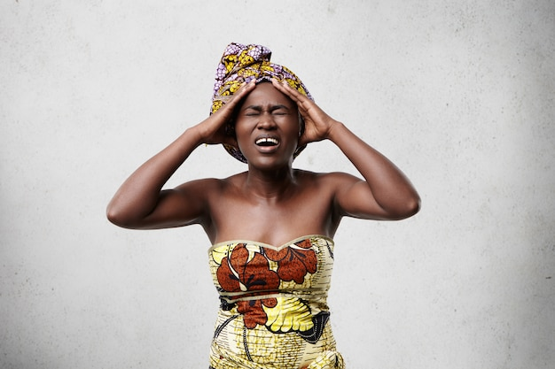 Portret van beklemtoonde afrikaanse vrouw die kleurrijke kleding draagt die hoofd met pijnlijke blik houdt terwijl het lijdt aan migraine of hoofdpijn.