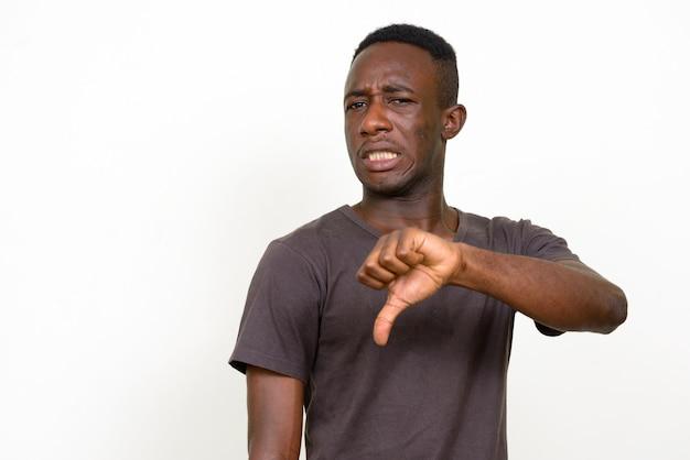 Portret van beklemtoonde jonge afrikaanse man die walgt met neer duimen kijkt