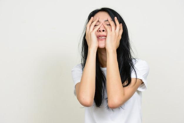 Portret van beklemtoonde jonge aziatische vrouw die geïrriteerd en gefrustreerd kijkt