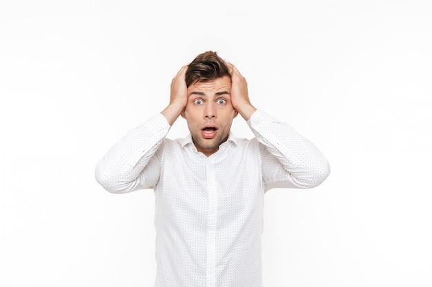 Portret van beklemtoonde jonge mens die zijn hoofd grijpt en probleem uitdrukt.
