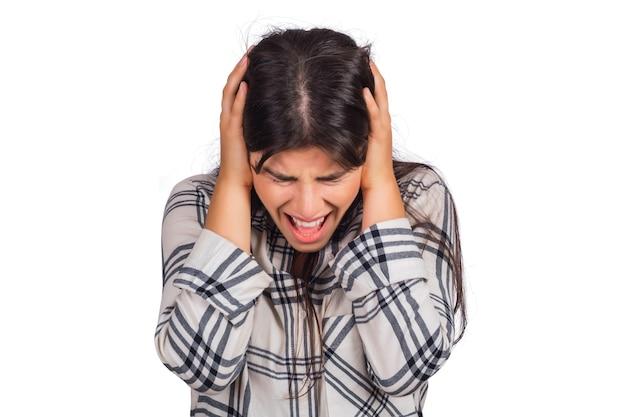 Portret van beklemtoonde jonge vrouw die hoofdpijn in studio lijdt.