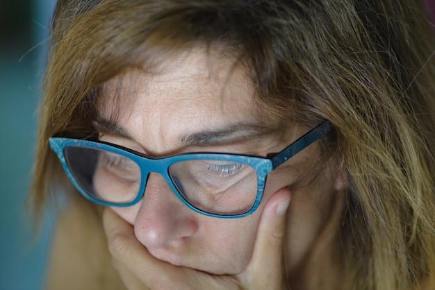 Portret van beklemtoonde rijpe vrouw die met hand op mond neer kijkt