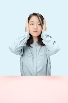 Portret van beklemtoonde vrouwenzitting met gesloten ogen en die met handen bedekken. geïsoleerd op blauwe studioachtergrond. ik hoor niets