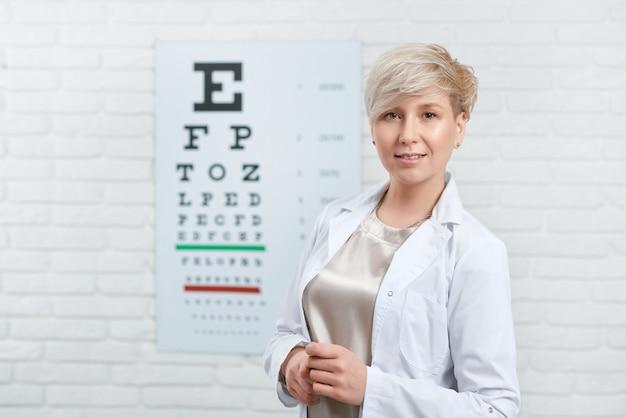Portret van bekwame oftalmoloog die voor visuele inspectietafel blijven