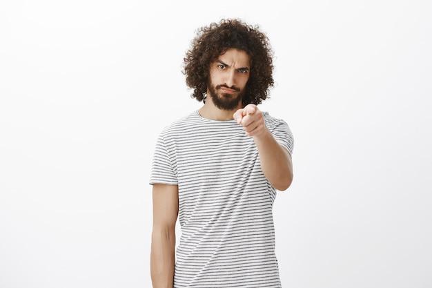 Portret van beledigde verontwaardigde knappe spaanse man met baard en afro-kapsel, wijzend met de schuld naar voren, fronsend en ontevreden onder het voorhoofd kijkend