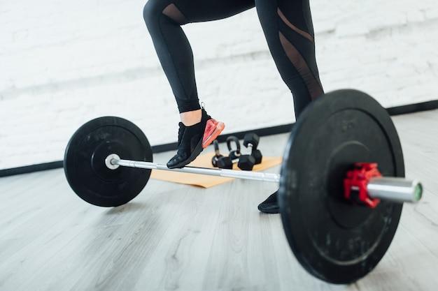 Portret van benen sportieve vrouw met barbell. isolatet op grijze vloer! levensstijl.