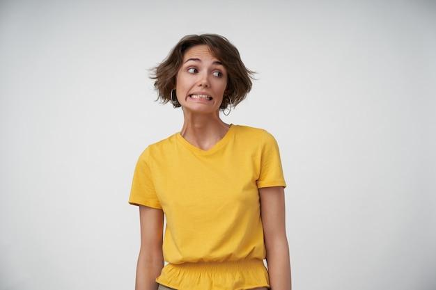 Portret van beschaamde jonge vrouwelijke dame met kort bruin haar opzij kijken en verward tanden tonen, handen langs haar lichaam houden tijdens het poseren