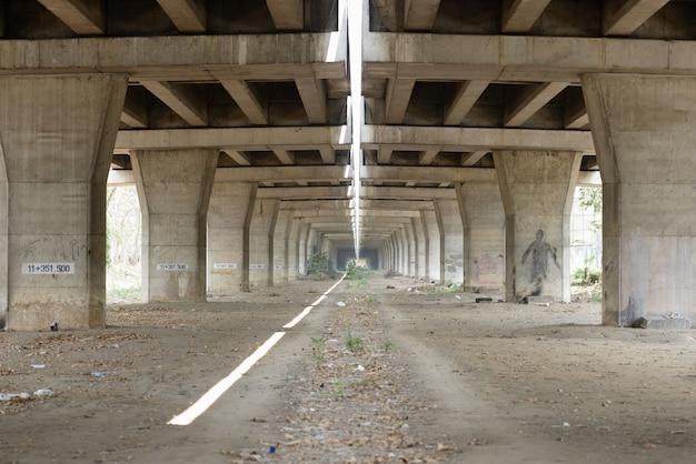Portret van betonnen brugpijlers onder de verhoogde sporen van de snelweg